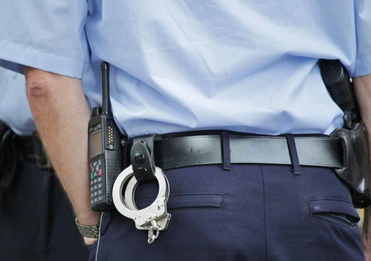 Amokmaker aangehouden - foto van agent met handboeien en vuurwapen
