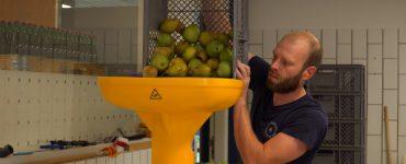 Samen met een collega van De Vergeten Appel is Johan Holleman druk in de weer in zijn productieruimte. Als je binnenstapt in zijn hal in Biezenmortel, is de zoete fruitlucht moeilijk te missen.