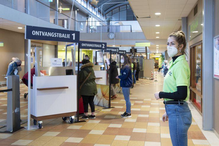 Stewards wijzen iedereen bij de nieuwe ontvangstbalies van het ETZ op de beschermingsmaatregelen en ontvangen de patiënten en bezoekers.